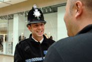 A male Police Officer talking to a member of the public