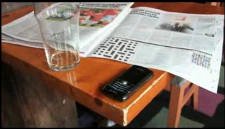 A mobile phone and newspaper on a table top