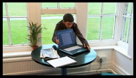 An opportunist thief spots a laptop next to an open window.