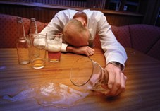 A man collapsed over a table with beer bootles and glasses surrounding