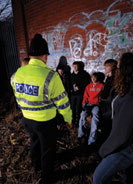 An officer approaching teenagers about grafitti